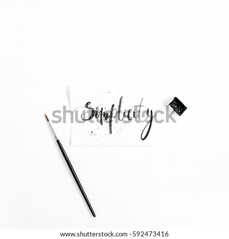 Minimalistic stylish composition with word Simplicity written in calligraphic style on paper with paint brush on white background. Flat lay, top view