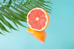 Minimalistic summer fruit tropical composition. Half of juicy fresh grapefruit and palm leaves with mirror image on blue background. Copy space.