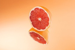 Minimalistic summer fruit tropical composition. Half of juicy fresh grapefruit with mirror image on bright orange background. Copy space.