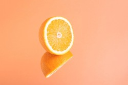 Minimalistic summer fruit tropical composition. Half of juicy fresh orange with mirror image on bright orange background. Copy space.
