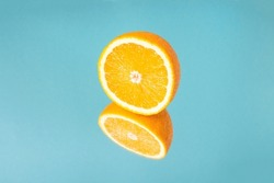 Minimalistic summer fruit tropical composition. Half of juicy fresh orange with mirror image on blue background. Copy space.