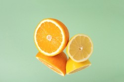 Minimalistic summer fruit tropical composition. Halves of juicy fresh orange and lemon with mirror image isolated on light green background. Copy space