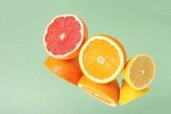Minimalistic summer fruit tropical composition. Halves of juicy fresh orange, lemon and grapefruit with mirror image isolated on light green background. Copy space.