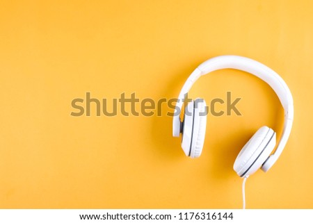 Minimalistic top view composition with white headphones on bright yellow background with a lot of copy space for your text. Close up,  flat lay.