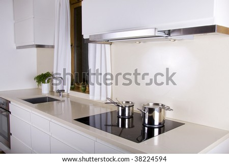 Minimalistic white kitchen with two sauce pans