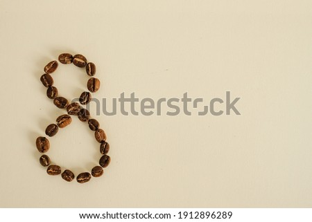 Minimalizm beige background.Eight of coffee beans for International Women's Day.Concept postcard, greeting, March 8.Flatlay.Close up.Copy spase. Stok fotoğraf ©