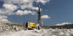 Mining drilling machine drills wells in a slate quarry, close-up, in preparation for blasting operations, panorama on the background of a quarry and a blue sky with clouds.