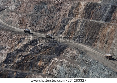 Mining trucks driving in the Kalgoorlie Super Pit gold mine.
