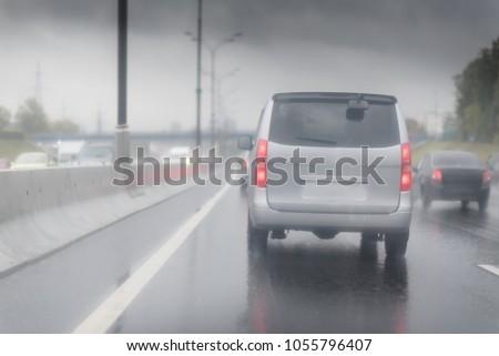 minivan car in rain on asphalt wet road. Gray Clouds on the sky . #1055796407