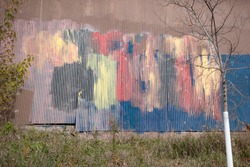 MINNEAPOLIS, MINNESOTA USA - OCTOBER 30, 2018: Metal corrugated siding decorated with a pastel of many colors on the bicycling Midtown Greenway trail.