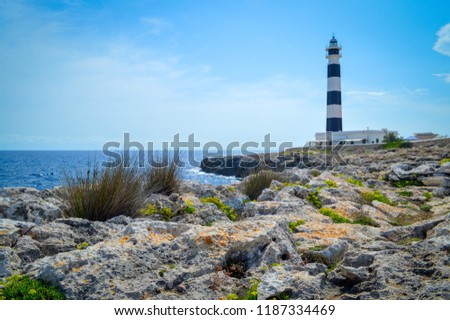 Minorca Lighthouse Cap de Artrutx cala n'bosch. Cami de cavalls. Beautiful coastal landscape with black and white lighthouse in the background and marine flora in the foreground Foto stock ©