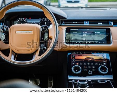 MINSK, BELARUS - AUGUST 7, 2018: Photo of Range Rover Velar's interior. Interior features caramel-browm leather trim on seats and dashboard. Range Rover Velar's cabin exudes elegant simplicity. #1151484200