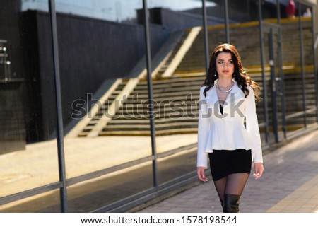 Minsk, Belarus - 11/10/2019. Dark-haired girl in town, long legs, white blouse, black skirt. #1578198544