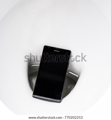 MINSK, BELARUS, February 1, 2017: Smartphone Sony Xperia SP dropped into a toilet bowl. Old phone model. #770202253