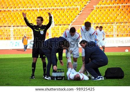 MINSK, BELARUS - MARCH 25:FC Bate Borisov VS FC MINSK, unidentified people providing first aid to injured player (FC MINSK) on March 25, 2012 in Minsk, Belarus