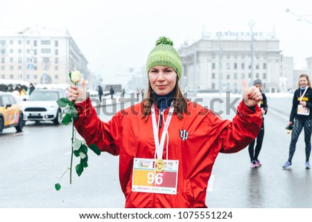 Minsk, Belarus. March 8, 2018 Women's Race Public action Women against violence Girl with flower stands outdoors #1075551224