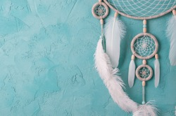 Mint cream dream catcher on turquoise textured background. Texture of concrete.