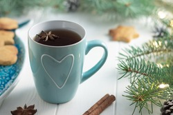 Mint cup of tea with heart, gingerbread next to branches of a Christmas tree with ight bulbs on white wooden background