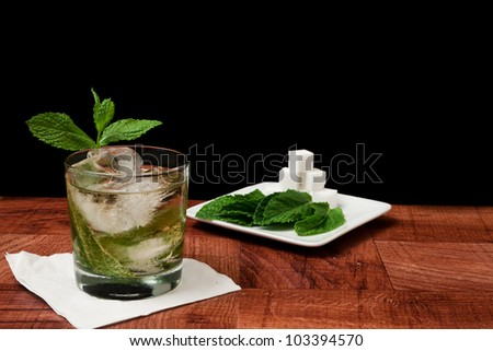 Mint julep isolated on a black background served on a bar top garnished with fresh mint