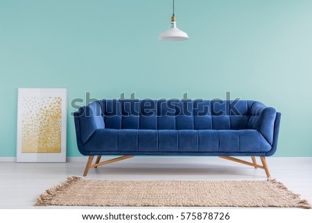 Mint living room with blue sofa, rug and lamp #575878726