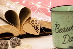 Mint tea mug. On the mug is the inscription of a beautiful day. Nearby lies an open book with heart-shaped pages. Garlands, a eucalyptus branch, decorative balls, and a wooden heart decorate the