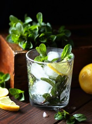 Mint with lemon citrus cocktail or mocktail with ice in glass on dark moody vintage wooden background, closeup, mojito drink, homemade beverage concept