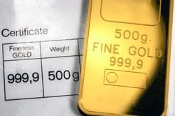 Minted gold bar weighing 500 grams on paper certificate background. Gold ingot with assay certificate.