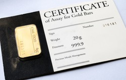 Minted gold bar weighing 20 grams with certificate in blister package.