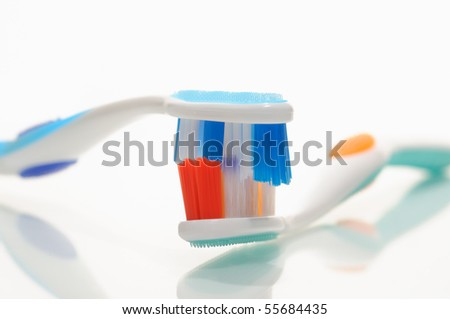 """Minty-Fresh Kiss. Two new, good looking toothbrushes """"kissing"""" . Humor, conceptâ?¦ - stock photo"""
