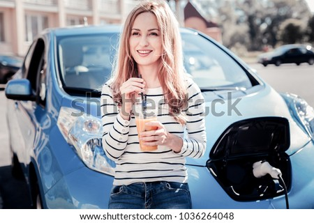 Minute of a rest. Satisfied pretty young woman standing near the car on the electric gas station looking aside and drinking juice.