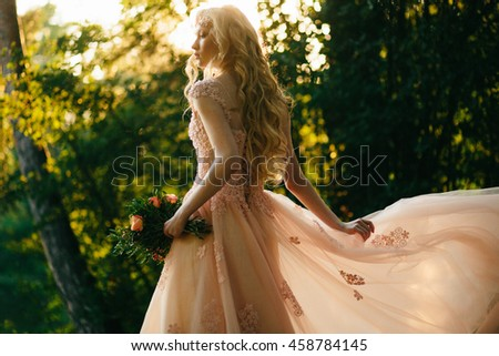 Miracle blonde in a long evening dress stands in a forest