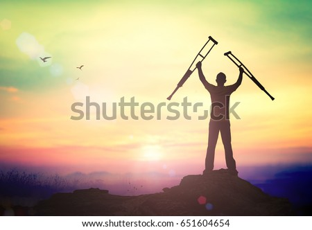 Miracle healing and recovery concept: Silhouette a disabled man standing up and raising his crutches at mountain autumn sunset background