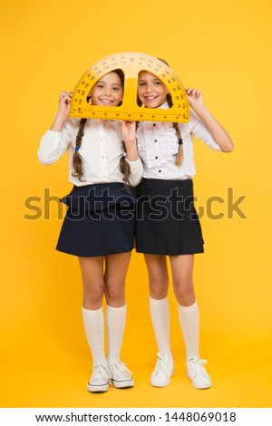 mired in geometry. Maths and geometry. Kids in uniform at yellow wall. friendship and sisterhood. happy small girls study mathematics. students use protractor ruler. stem disciplines. back to school.