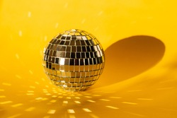 mirror ball on a yellow background, glare from a mirror ball, sun glare on a colored background