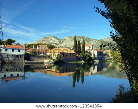 Mirror image of the old buildings in the town of Trebinje, Bosnia and Herzegovina in the water of the river.