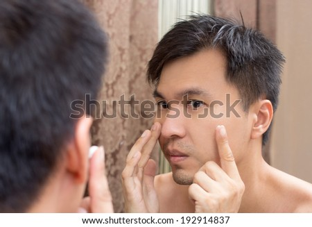 Mirror reflection of a young asian handsome man applying facial cream on face