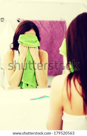 Mirror reflection of a young woman wiping her face with a green towel in the bathroom.