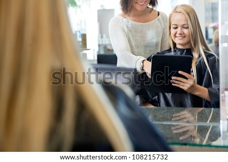 Mirror reflection of female customer holding digital tablet with hairdresser standing behind her