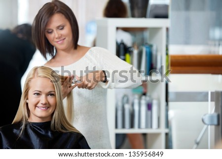 Mirror reflection of hairdresser giving a haircut to woman at parlor - stock photo