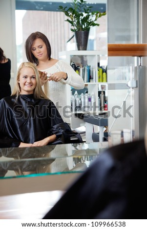 Mirror reflection of hairdresser giving young woman a new haircut at parlor