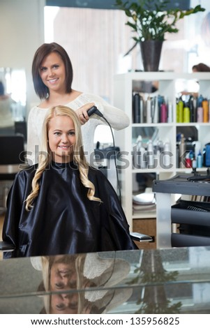 Mirror reflection of stylist curling hair of young woman at parlor