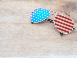 mirror sunglasses with american flag pattern on wooden background.4th of July concept. Happy flag day.