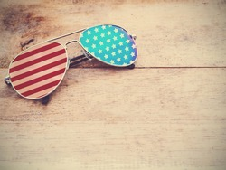 mirror sunglasses with american flag pattern on wooden background.4th of July concept. Vintage filter effect. Happy flag day.