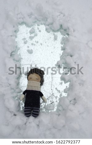 Mirror window in the snow with an interior doll in gray clothes and a knitted hat in the foreground
