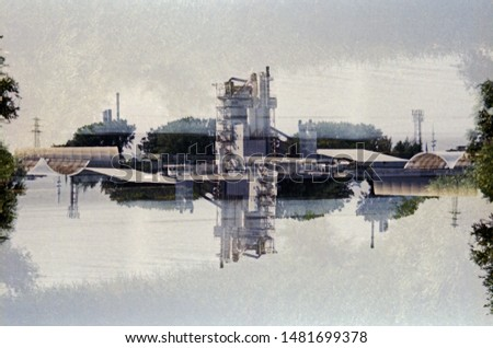 Mirrored analog color negative double exposure of industrial buildings on a summer day.