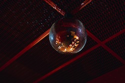 mirrored disco ball attached to the red ceiling. disco party entertainment