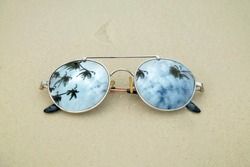Mirrored sunglasses close up on the beach sand with palm trees reflection.