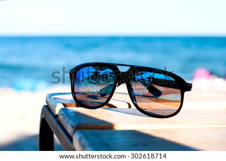 mirrored sunglasses on the table on the beach with sea views
