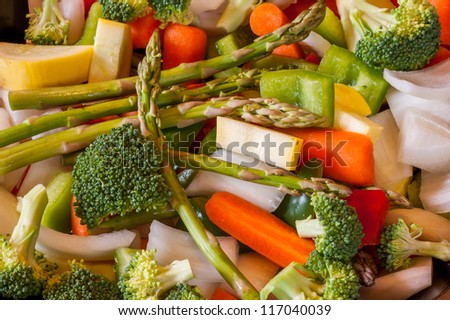 Miscellaneous fresh vegetables cut up in pieces ready for stir fry or saute. It includes carrots, broccoli, onions, asparagus, squash, and red and green pepper for healthy eating
