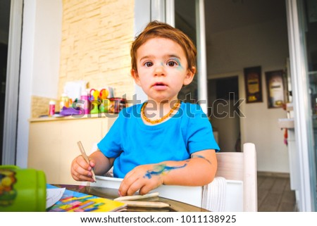 Mischievous baby blue color markers innocent face painted child . #1011138925